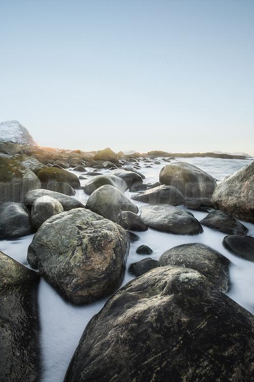 White foam from the sea encircles the golden stones at the beach | Hvitt skum fra havet omfavner de gyldne stenene på stranden