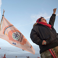 Vanessa Dundon from White Cone raises her fist in solidarity of the DAPL protest to a car driving by in Standing Rock, ND Monday.Protestors from around the world have added their flags to the fence lining county road 1806 to show support for the people of Standing Rock protesting the pipeline.