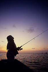 Stock photo of the silhouette of a woman fishing from  a pier at sunset