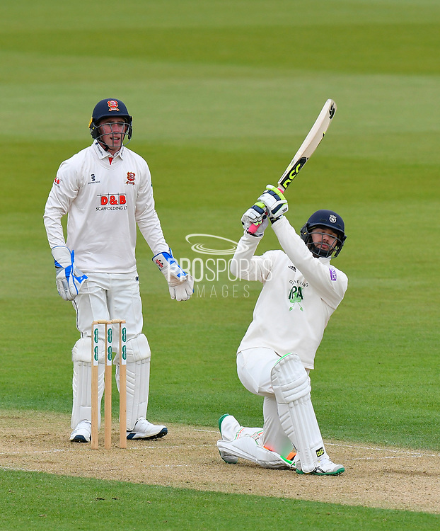 Rilee Rossouw of Hampshire hits the ball over the boundary for six runs watched by stand in wicket keeper Dan Lawrence of Essex during the first day of the Specsavers County Champ Div 1 match between Hampshire County Cricket Club and Essex County Cricket Club at the Ageas Bowl, Southampton, United Kingdom on 5 April 2019.