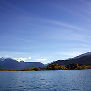 The pristine waters of Lake Wakatipu at Glenorchy in Autumn..Glenorchy is a small settlement nestled in spectacular scenery at the northern end of Lake Wakatipu in New Zealand's south Island. It is approximately 45 kilometres by road or boat from Queenstown, the nearest large town..Glenorchy is a popular tourist spot, close to many tramping tracks. It lies near the borders of Mount Aspiring National Park and Fiordland National Park. The local scenery received worldwide attention when it was used as one of the settings in the first of Peter Jackson's Lord of the Rings films. Glenorchy is the home of  Dart River Jet Safaris. The  unique adventure combines exhilarating wilderness jet boating with unique Funyak inflatable canoes used to explore the magnificent World Heritage wilderness within Mt Aspiring National Park. Professional guides take participants through dramatic landscapes, paddling along channels of the glacier fed Dart River's braided river system as well as along hidden side streams, rock pools and dramatic chasms. Glenorchy, New Zealand. 13th April 2011. Photo Tim Clayton..