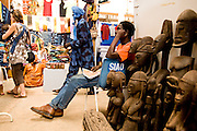 A vendor selling wooden statues wait in his stand while customers walk by at the 22nd Salon International de l'Artisanat de Ouagadougou (SIAO) in Ouagadougou, Burkina Faso on Saturday November 1, 2008.