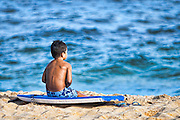 A young boy sitting on a surfboard waits his turn to go into the ocean.