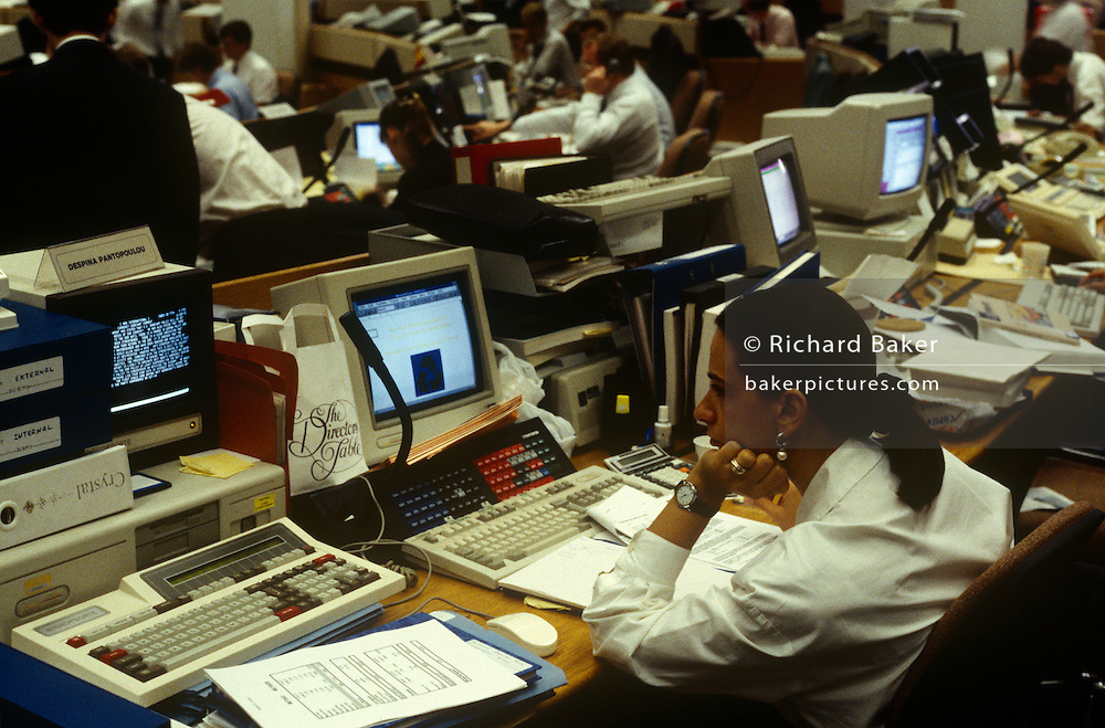 An interior of office desks and 90s computers in the currency trading floor of National Westminster Bank PLC in the City of London, the capital's financial centre. Screens glow with the most up to date trading figures and news items allowing traders to react instantly on the money markets. A lady employee stares at her data near a large keyboard and hard drives and deep monitors were state of the art technology in the early 1990s.