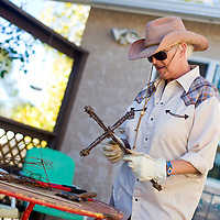 110112       Brian Leddy<br /> Mar Heifner makes a cross out of barbed wire at her home. Heifner is one of several area artists participating in the Recycled Arts and Crafts show this weekend.