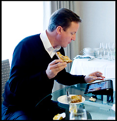 The Prime Minister David Cameron has a piece of toast and checks the web on an Ipad in his hotel room at the Conservative Party Conference in Birmingham, Tuesday October 5,  2010. Photo By Andrew Parsons/ i-Images  ..Byline Mandatory