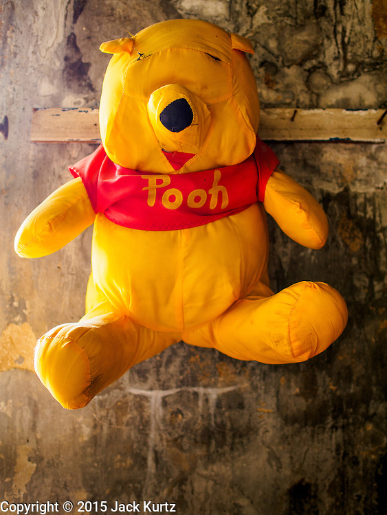 17 MARCH 2015 - BANGKOK, THAILAND: A stuffed Winnie the Pooh bear hanging in a hallway in the old Customs House in Bangkok. The old Customs House was once the financial gateway to Thailand (before 1932 called Siam). It was designed by an Italian architect in the 1880s. In the 1950s, customs moved to new, more modern building and the Customs House became the headquarters for the Marine firefighters. The firefighters now live in the decrepit buildings with their families.    PHOTO BY JACK KURTZ
