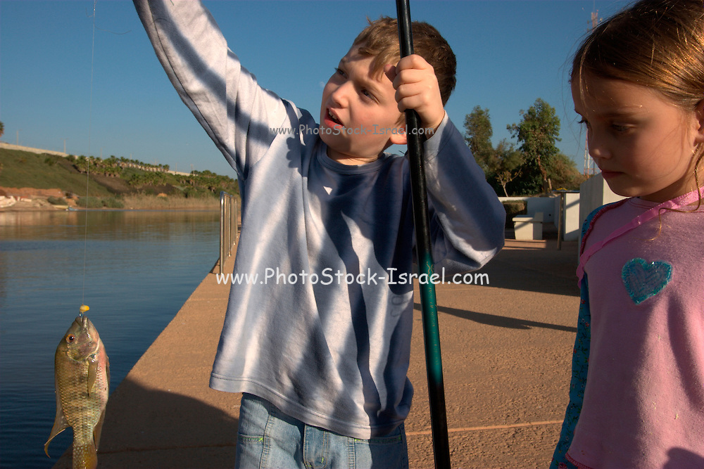 Israel, Hadera, The Hadera River. Children fishing in the river. Model Release available