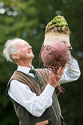 © Licensed to London News Pictures. 16/09/2016. Harrogate UK. Picture shows Peter Glazebrook & his prize winning beetroot that weighed 11.5 kg at the Giant vegetable competition in Harrogate. The competition see's competitors from across the UK show their biggest Carrot's, Cucumbers, Cabbages, Onion's & Tomatoes competing for the title of heaviest & longest at the Harrogate Autumn Flower Show. Photo credit: Andrew McCaren/LNP