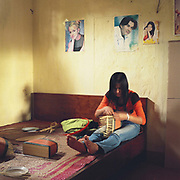 A young woman weaving bamboo baskets sitting on a bed at home in Phu Vinh, Ha Tay province, Vietnam. With Vietnam's growing population making less land available for farmers to work, families unable to sustain themselves are turning to the creation of various products in rural areas.  These 'craft' villages specialise in a single product or activity, anything from palm leaf hats to incense sticks, or from noodle making to snake-catching. Some of these 'craft' villages date back hundreds of years, whilst others are a more recent response to enable rural farmers to earn much needed extra income.