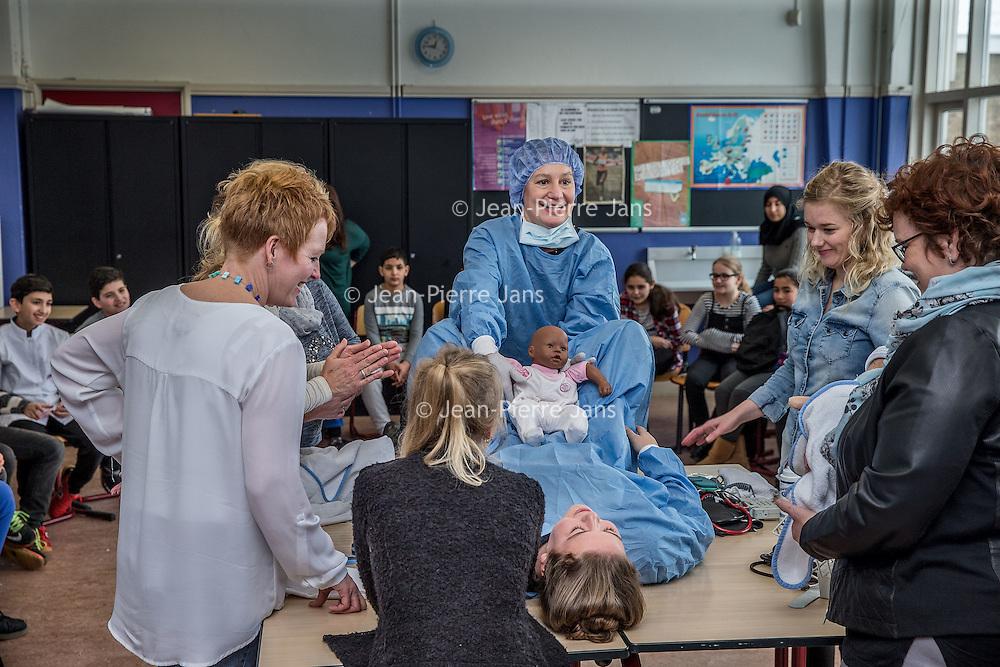 Nederland, Amsterdam, 12 februari 2017.<br /> Gynaecologieles aan kinderen met een achterstandspositie op de weekendschool Bredero College in Amsterdam Noord.<br /> Op de foto: Tijdens de les wordt een spoedbevalling nagebootst.<br /> <br /> <br /> Foto: Jean-Pierre Jans