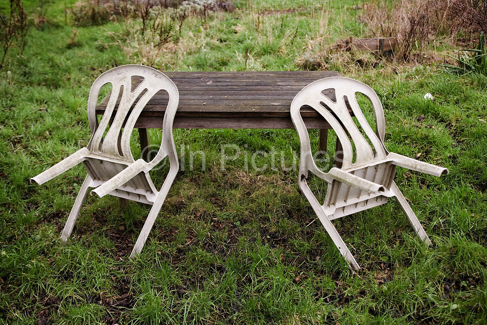 Chairs resting on a garden table in a North London allotment, 11th January 2007, London, United Kingdom. Allotments have now been around for centuries, a simple plot of land rented and cherished by an individual typically used for growing vegetables or flowers. However for some allotmenteers, their 10 poles sized plot can mean a whole lot more than just the need to grow a few spuds. Some see their plot as their sanctuary, a place of therapy and peace of mind, where one can enjoy the simplicity of nature and wildlife.