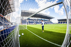 Falkirk FC keeper Michael McGovern seen through the net during the warm-up.The Falkirk Stadium, with the new pitch work for the Scottish Championship game v Morton. The woven GreenFields MX synthetic turf and the surface has been specifically designed for football with 50mm tufts compared with the longer 65mm which has been used for mixed football and rugby uses.  It is fully FFA two star compliant and conforms to rules laid out by the SPL and SFL.<br /> ©Michael Schofield.