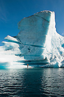 A man stand up paddle boards (SUP) in front of a towering iceberg on Bear Lake in Kenai Fjords National Park, Alaska.