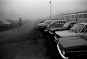 Lone commuter heads for the station on a foggy morning in Golders Green Underground station car park. Coming and Going is a project commissioned by the Museum of London for photographer Barry Lewis in 1976 to document the transport system as it is used by passengers and commuters using public transport by trains, tubes and buses in London, UK.