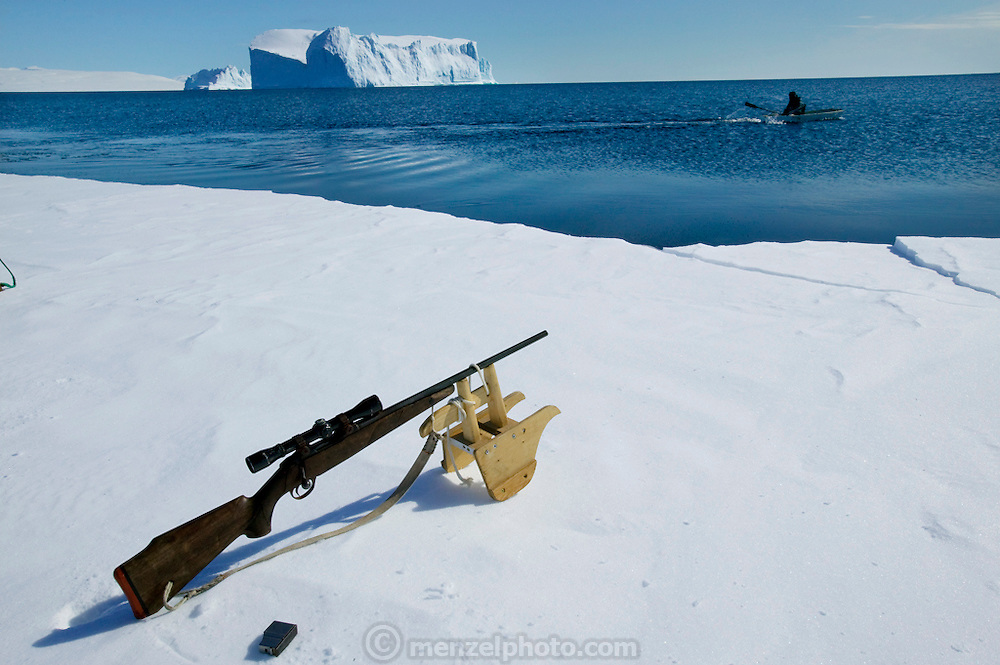 Seal hunter Emil Madsen's rifle tied to a wooden stand during one of his hunting trips near his home in Cap Hope, Greenland. (Emil Madsen is featured in the book What I Eat: Around the World in 80 Diets.) He has just shot a seal and is rowing his small plywood boat out to haul it in before it sinks out of sight and reach. Unfortunately he did not reach this seal in time and it was lost beneath the ring of blood on the clear arctic sea. Seal meat continues to be an important source of meat for some Greenlanders, but for many, Danish food has replaced it in the native diet.