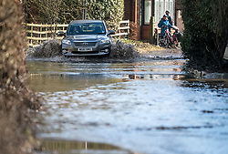 © Licensed to London News Pictures. 03/02/2021. Sonning, UK. A car ploughs through flood water in the village of Sonning in Berkshire, where the RiverThames has broken its banks.  Large parts of the UK experience more wet conditions which is expected to bring further flooding. Photo credit: Ben Cawthra/LNP