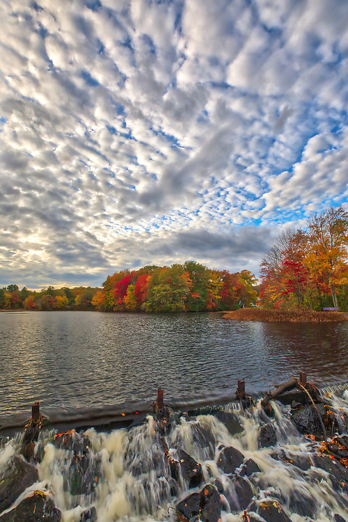 Fall foliage peak colors at Mill Pond in Ashland, Massachusetts, the overflowing water with surrounding trees covered in beautiful New England colors.<br /> <br /> Massachusetts Mill Pond in Ashland photography images are available as museum quality photography prints, canvas prints, acrylic prints or metal prints. Prints may be framed and matted to the individual liking and room decor needs at <br /> <br /> https://juergen-roth.pixels.com/featured/ashland-mill-pond-dam-juergen-roth.html<br /> <br /> All autumn photography images are available for picture image licensing at www.RothGalleries.com.<br /> <br /> Good light and happy photo making!<br /> <br /> My best,<br /> <br /> Juergen<br /> Image Licensing: http://www.RothGalleries.com<br /> Fine Art Prints: http://fineartamerica.com/profiles/juergen-roth.html<br /> Photo Blog: http://whereintheworldisjuergen.blogspot.com<br /> Twitter: https://twitter.com/naturefineart<br /> Facebook: https://www.facebook.com/naturefineart<br /> Instagram: https://www.instagram.com/rothgalleries