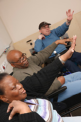 Service users, some in wheelchairs, doing specially adapted exercises for limited mobility at resource for people with physical and sensory impairment.