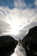 A hiker leaps over a tidepool - Shi Shi Point of Arches - Olympic National Park - Washington State