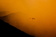A firefighting helicopter flies into thick smoke, a dangerous maneuver without visability in hilly territory, at the La Brea Fire in California. Firefighters are constantly balancing the risks of flying at night, in smoke or high wind, with the benefits of being able to use air support to fight fire.