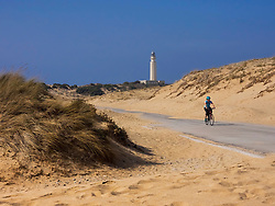 Mature woman cycling on road by sand dune