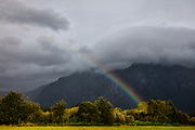 A rainstorm sits at the summit of Mount Si, resulting in a rainbow that falls at the mountain's base in North Bend, Washington. Mount Si is a 4,167-foot (1,270 meter) mountain that is a remnant of an oceanic plate volcano. It lies at the western edge of the Cascade Range of mountains.