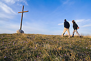 Liana and Parmenter Welty walk towards a large cross on top of a hill above the village of O Cebreiro, Galicia, Spain, along the Camino de Santiago pilgrimage.