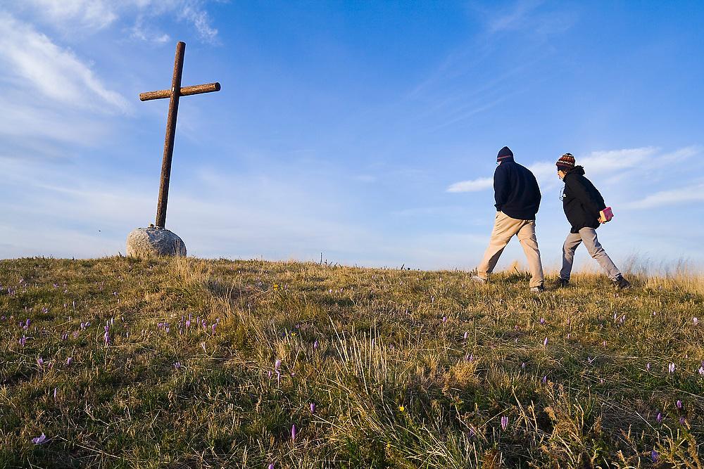 Liana and Parmenter Welty walk towards a large cross on top of a hill above the village of O Cebreiro, Galicia, Spain, along the Camino de Santiago pilgrimage.