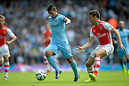 Manchester City's Sergio Aguero in action with Arsenal's Laurent Koscielny chasing. Barclays Premier league match, Arsenal v Manchester city at the Emirates Stadium in London on Saturday 13th Sept 2014.<br /> pic by John Patrick Fletcher, Andrew Orchard sports photography.