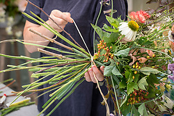 Rachel Siegfried making a hand tied  flower arrangement. Tying stems together.