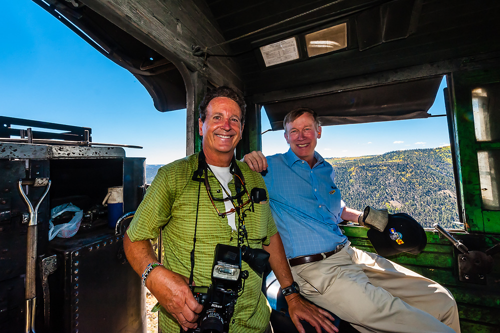Photographer Blaine Harrington III and Governor John Hickenlooper of Colorado riding in the steam locomotive of the Cumbres & Toltec Scenic Railroad in southern Colorado.