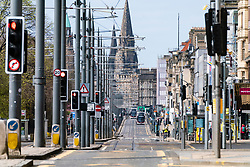 Edinburgh, Scotland, UK. 18 April 2020. Views of empty streets and members of the public outside on another Saturday during the coronavirus lockdown in Edinburgh. View along an almost deserted Princes Street. Iain Masterton/Alamy Live News