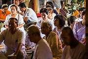 "25 FEBRUARY 2013 - BANGKOK, THAILAND:  Thai Buddhists gather in Wat Benchamabophit Dusitvanaram (popularly known as either Wat Bencha or the Marble Temple) to listen to the abbot speak on Makha Bucha Day. Makha Bucha is a Buddhist holiday celebrated in Myanmar (Burma), Thailand, Cambodia and Laos on the full moon day of the third lunar month (February 25 in 2013). The third lunar month is known in Thai is Makha. Bucha is a Thai word meaning ""to venerate"" or ""to honor"". Makha Bucha Day is for the veneration of Buddha and his teachings on the full moon day of the third lunar month. Makha Bucha Day marks the day that 1,250 Arahata spontaneously came to see the Buddha. The Buddha in turn laid down the principles his teachings. In Thailand, this teaching has been dubbed the 'Heart of Buddhism'.     PHOTO BY JACK KURTZ"