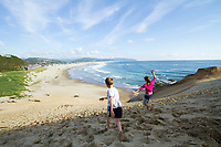 Kids playing on sand dune in Pacific City, OR. Model released.