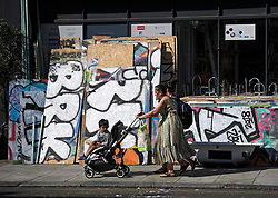 © Licensed to London News Pictures. 23/08/2019. London, UK. Graffiti covered boards lie in the street waiting to be used to protect buildings, ahead of the 2018 Notting Hill Carnival which starts this weekend. Warm weather is expected over the bank holiday weekend with carnival attracting over 1 million people to the capital. Photo credit: Ben Cawthra/LNP