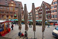 DEU, Deutschland, Germany, Tübingen, 09.04.2021: Eine Familie verweilt auf dem Tübinger Marktplatz unter den zugeklappten Sonnenschirmen eines geschlossenen Cafés. Die Außengastronomie in Tübingen musste wieder schließen, weil zuviele auswärtige Gäste die Stadt besuchten. In einem Modellversuch war es auch für auswärtige Besucher möglich, an Teststationen im Stadtgebiet einen Corona-Schnelltest machen zu lassen und bei negativem Ergebnis ein digitales Tagesticket zu erhalten, das sie einen Tag lang dazu berechtigt, in den geöffneten Tübinger Geschäften einkaufen zu gehen oder die Außengastronomie von Restaurants und Cafés zu nutzen.