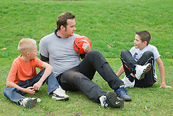 Man and boys with football.