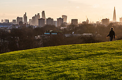December 11th 2014. With London's early morning skyline as a backdrop, a commuter makes his way to work on Primrose Hill.