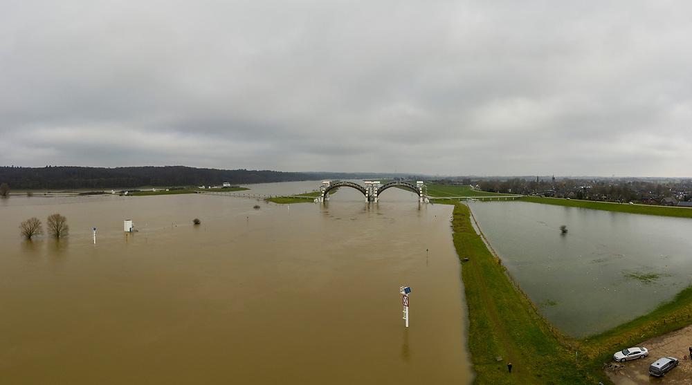 Nederland, Gelderland, Nijmegen, 04-002-2021; Hoog wNederland, Gelderland, Gemeente Overbetuwe, 04-002-2021; Hoog water bij de stuw bij Driel in de Neder-rijn. In verband met het hoge water ten gevolge van overvloedige regenval en smeltwater bij de bovenloop van de rivier de Rijn, heeft ook de benedenloop - de Nederrijn - met hoge waterstanden te maken. Daarom is de vizierschuif van de stuw is geopend. De stuw bij Driel, de Kraan van Nederland, zorgt voor afvoer van het water van de Rijn via Nederrijn en Lek.<br /> High water at the weir at Driel in the Lower Rhine. Due to high waters caused by abundant rainfall and meltwater at the upper coures of the river Rhine, the Lower Rhine also has to deal with high water levels. Therefore, the visor slide of the weir has been opened. The weir at Driel, the Kraan van Nederland, provides drainage of the water from the Rhine via Nederrijn and Lek.<br /> drone-opname (luchtopname, toeslag op standaard tarieven);<br /> drone recording (aerial, additional fee required);<br /> copyright foto/photo Siebe Swart