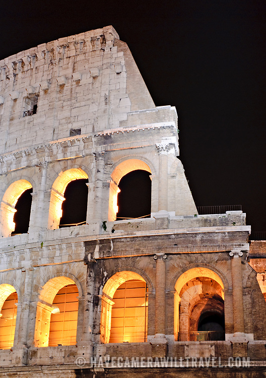 ROME, Italy - A telephoto shot of part of the ruins of the Coliseum of Rome, Italy, under lights at night.