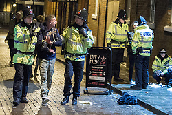 """© Licensed to London News Pictures . 15/12/2012 . Manchester , UK . Police detain a man and speak to a woman . Revellers enjoy a wet but busy night out on one of the last weekends before Christmas , a traditionally busy time when office parties and clubbers decent on bars and clubs , often known as """" Mad Friday """" . Photo credit : Joel Goodman/LNP"""