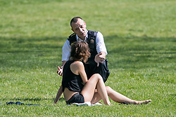 © Licensed to London News Pictures. 10/04/2020. London, UK. A Police officer speaks to a woman sun bathing on Primrose Hill in London, during a pandemic outbreak of the Coronavirus COVID-19 disease. The public have been told they can only leave their homes when absolutely essential, in an attempt to fight the spread of coronavirus COVID-19 disease. Photo credit: Ben Cawthra/LNP