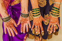 The decorated arms and hands of two women at a Hindu Indian wedding. Pune, India.