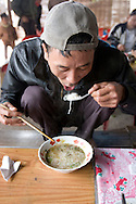 Portrait of a vietnamese man eating noodle soup, squatted on a bench. Vietnam, Asia.