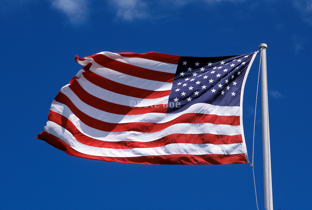 American flag blowing in a blue sky