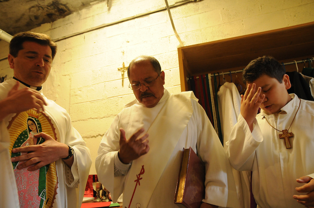 Father Franco Liporace (L) leads Deacon Willie Mendizabal and alter server Pedro Castro in prayer before beginning a weekly mass in the parish gymnasium.