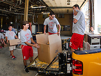 Coach Craig Kozens, Jacob Filgate, Jordan Audet and Tyler Mitza help load furniture and supplies for storage during construction phase of the Laconia Fire Department on Friday morning.  (Karen Bobotas/for the Laconia Daily Sun)