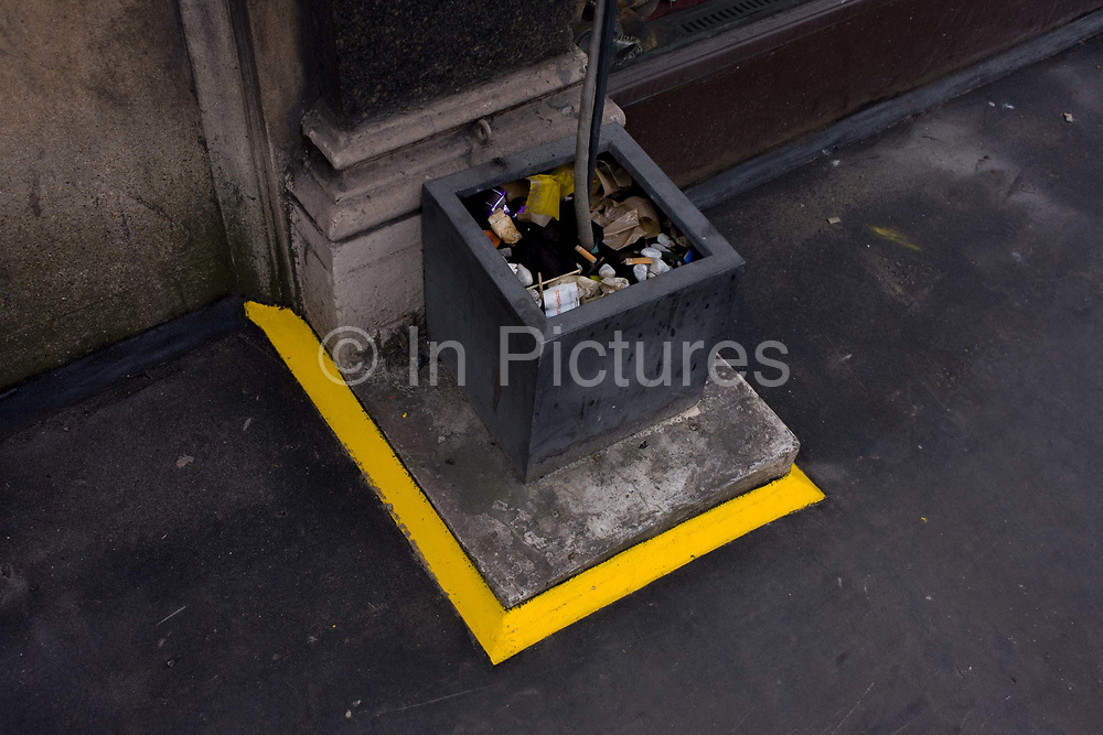 Yellow-painted square surrounds a dying potted plant in a central London street. The detail is of angles and lines, of bright colour in a landscape of otherwise drab shades of grey. Someone has clearly decided that the potted plant is a danger to the unwary who might trip up. The yellow is then, a warning to the dangers of pavement hazards.