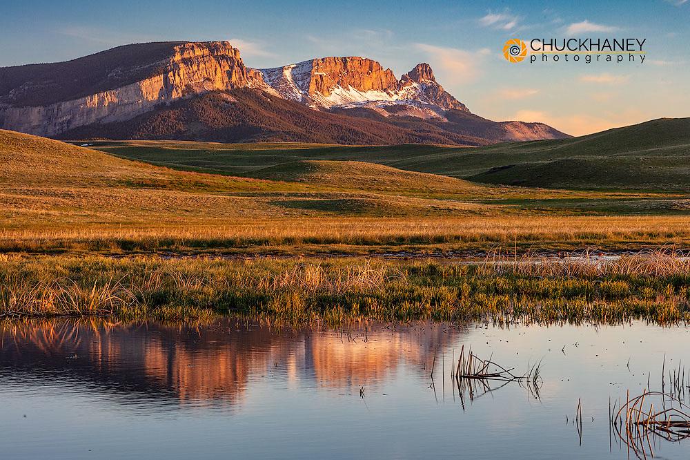 Sawtooth Ridge reflects into wetlands along the Rocky Mountain Front near Augusta, Montana, USA